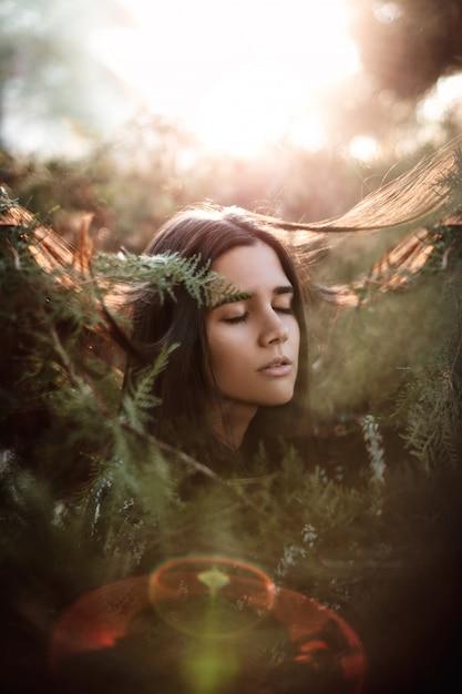 バックライトとフレアを右見て隔離されたブッシュの目を閉じて若い美しい女性 Premium写真