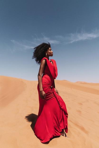 サハラ砂漠の赤いドレスと砂丘のアフリカの女性の肖像画 Premium写真