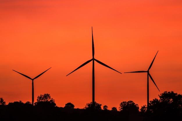 グリーンエネルギーの概念。夕焼け空に風力発電機 Premium写真