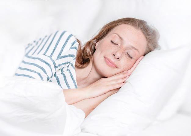 Молодая женщина спит в постели Premium Фотографии