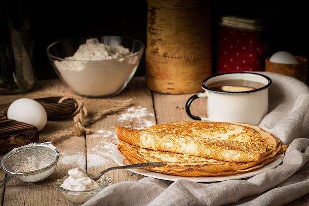 Стек блины и ингредиенты для приготовления пищи на столе Premium Фотографии