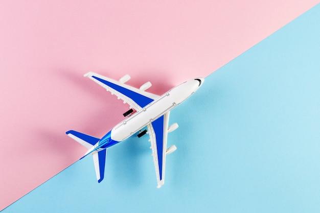 模型飛行機、ピンクとブルーの背景の飛行機。夏の旅行のコンセプト Premium写真