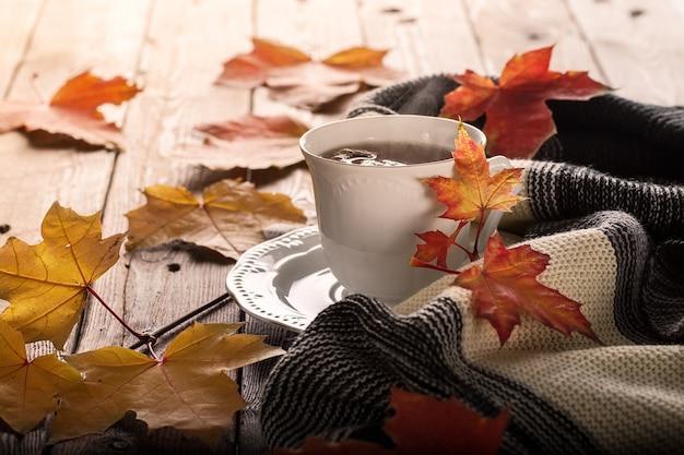 紅葉と木製のテーブルの上の紅茶のカップ。 Premium写真