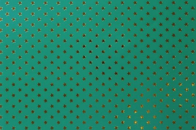 金色の星のパターンを持つ金属箔紙から濃い緑色の背景。 Premium写真