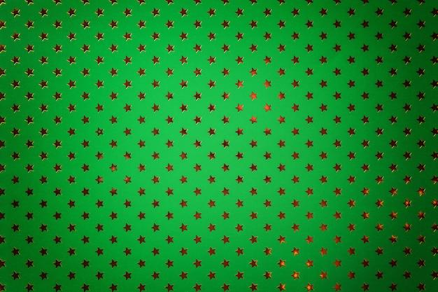 金色の星を持つ金属箔紙から濃い緑色の背景 Premium写真