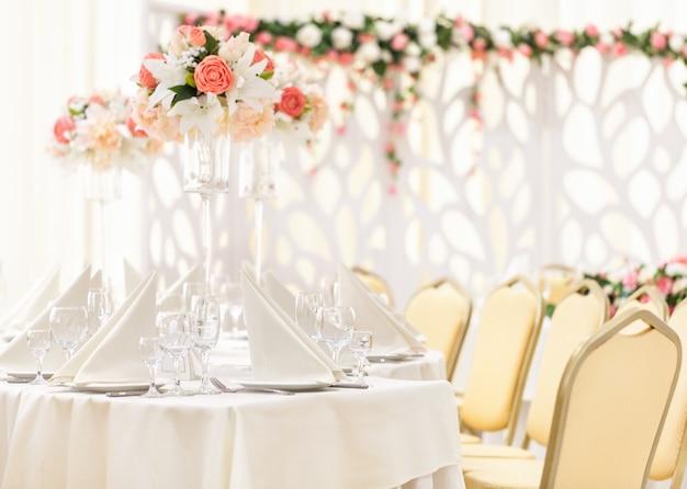 Сервированный стол для праздничного ужина со столовыми приборами и бокалами, украшенный цветочными композициями в вазах. Premium Фотографии