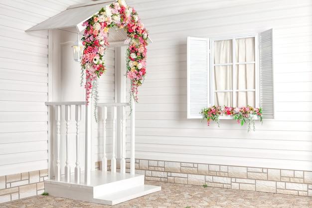 花と白いポーチのある白い家。プロヴァンス Premium写真