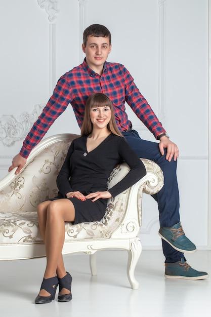 ソファに座っている若いカップルの家族の肖像画 Premium写真