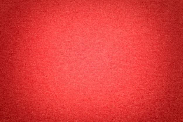 古い鮮やかな赤い紙の背景、クローズアップの質感。密集したボール紙の構造 Premium写真