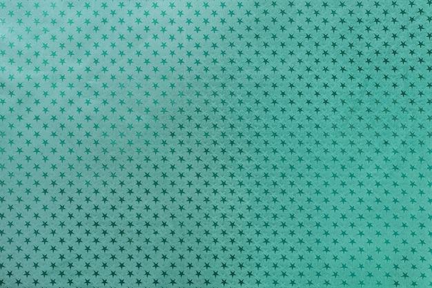 星のパターンを持つ金属箔紙から暗い青緑色の背景 Premium写真
