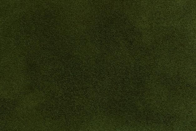 濃い緑色のスエード生地のクローズアップの背景。オリーブヌバックテキスタイルのベルベットマットテクスチャ Premium写真