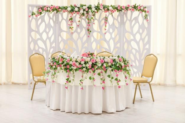 花の組成とパステルカラーのアーチで飾られた新婚夫婦のメインテーブル Premium写真