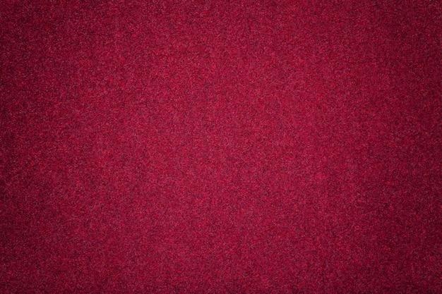 ダークレッドのマットスエード生地のクローズアップ。フェルトのベルベットの質感。 Premium写真