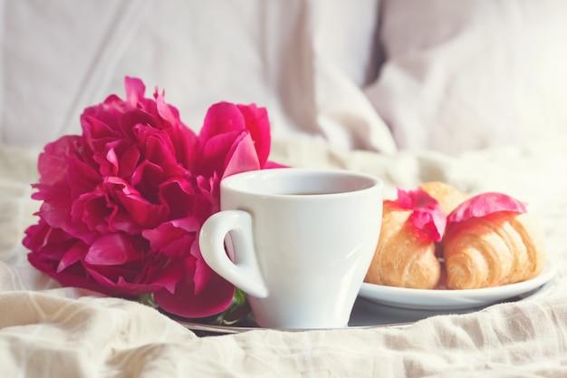 コーヒーカップ、クロワッサン、花の朝食 Premium写真
