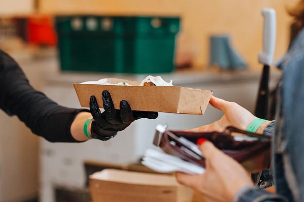 Продавец дает покупателю еду на уличном рынке Premium Фотографии