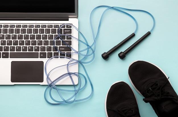 Плоский лежал вид сверху ноутбук с спортивного инвентаря на синем фоне. Premium Фотографии