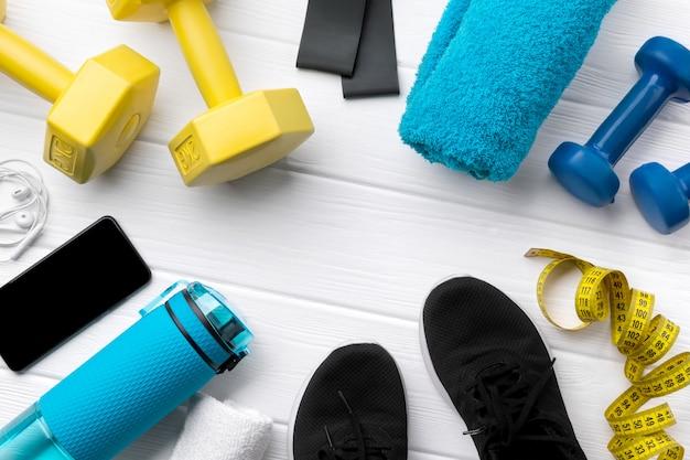 Плоские лежал вид сверху спортивного инвентаря, кроссовок и смартфонов на белом фоне деревянных Premium Фотографии
