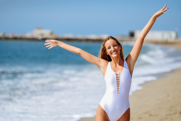 開いた腕を持つ熱帯のビーチの白い水着で若いブロンドの女性。 無料写真
