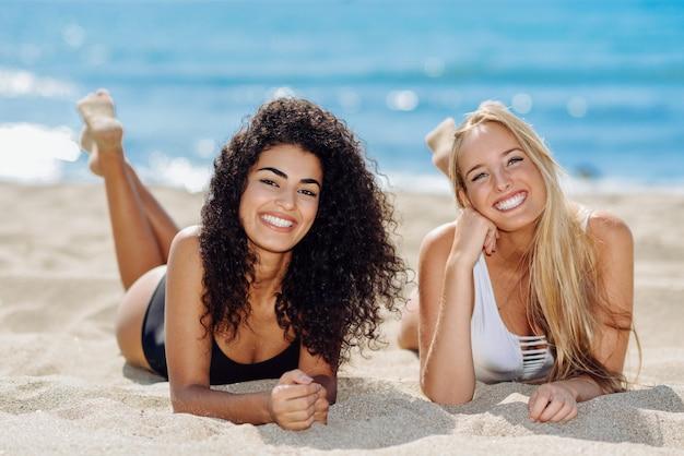 Две молодые женщины с красивыми телами в купальниках на тропическом пляже. Бесплатные Фотографии