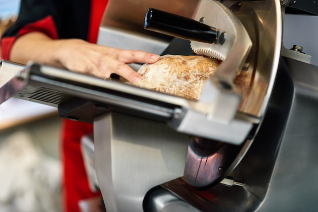 Женская мясная рулетка ветчины в режущей машине Бесплатные Фотографии