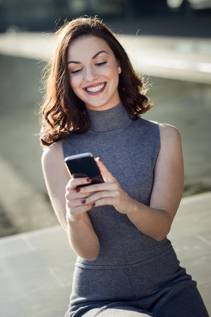 晴れた日にスマートフォンで魅力的な女性 無料写真