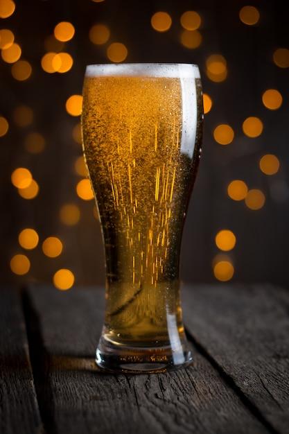 暗いテーブルの上のガラスのビール Premium写真