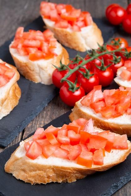 石のプレートにチェリートマトと伝統的なイタリアのブルスケッタ Premium写真