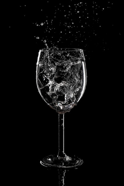 Всплеск воды в стакане на черном фоне Premium Фотографии