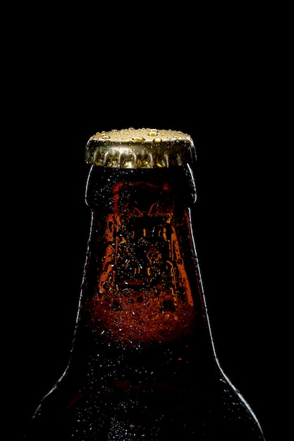 黒の背景にビール瓶のクローズアップのキャップ Premium写真