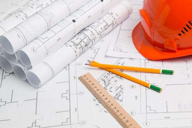 紙の建築図面、青写真、鉛筆、定規、ヘルメット。エンジニアリング設計図 Premium写真