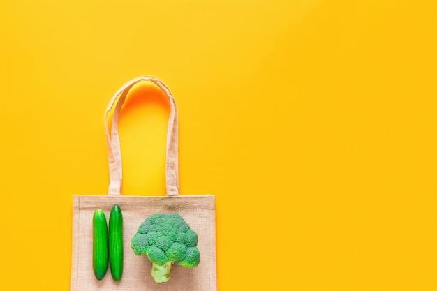 黄色の背景に新鮮な緑の野菜と再利用可能なテキスタイルショッピングバッグのトップビュー Premium写真