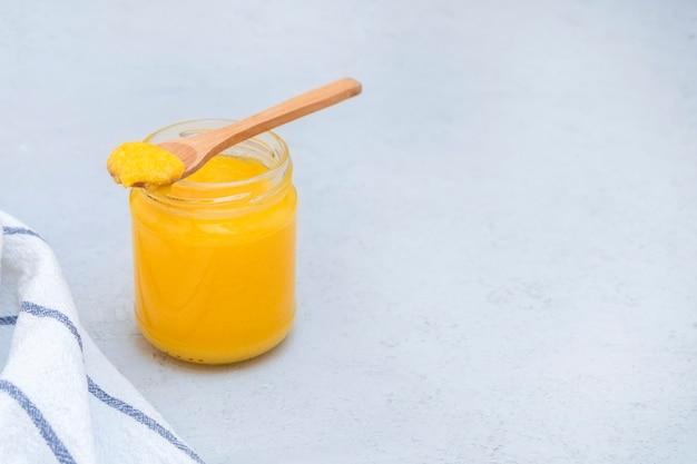 コンクリートのテーブルに木のスプーンで健康的な自家製ギーバターのガラスの瓶 Premium写真