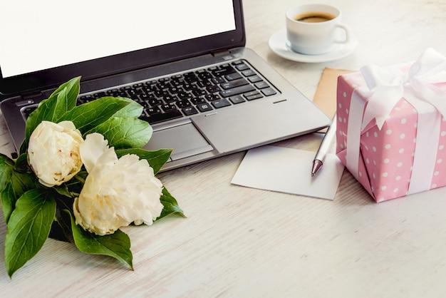 Взгляд со стороны палубы с компьютером, букета цветков пионов, чашки кофе, пустой карточки и розовой поставленной точки подарочной коробки. Premium Фотографии