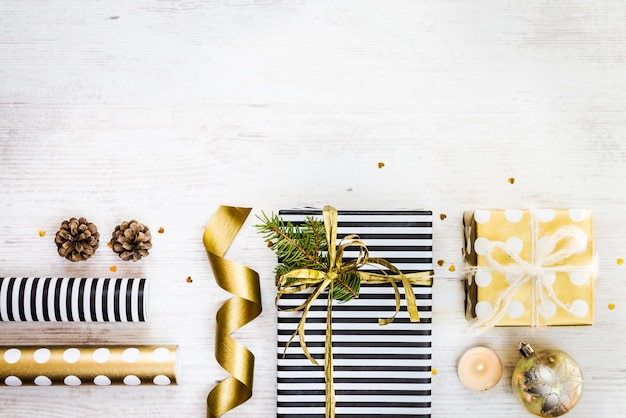 Подарочные коробки, обернутые в черно-белую полосатую и золотую пунктирную бумагу с сосной, шишками, свечами и оберточными материалами на белом фоне старого дерева. подготовка рождественских подарков. пустое пространство. Premium Фотографии