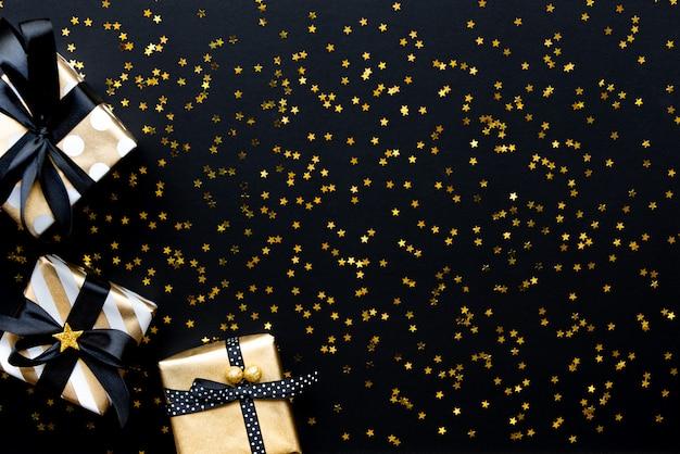 Подарочная коробка над звездой в форме золотых блесток на черном фоне. Premium Фотографии