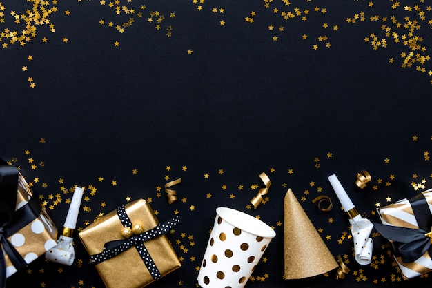 黒い背景に星形の金色のスパンコールにさまざまな金パターンの包装紙やパーティーアクセサリーのギフトボックス。 Premium写真