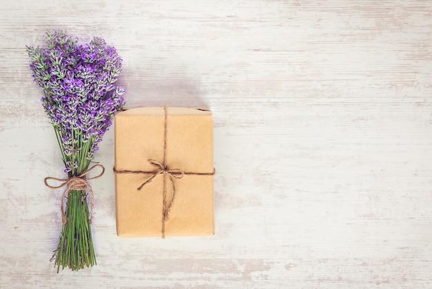 白い木製の素朴な背景の上のクラフト紙とラベンダーの花束に包まれたギフトボックスのトップビュー Premium写真