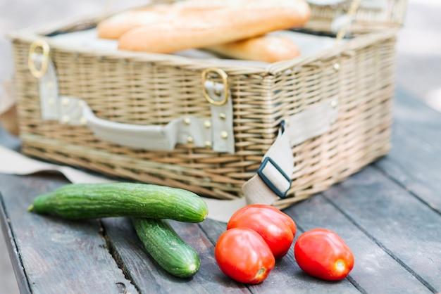 開いているピクニックバスケットの前に木製のテーブルの上のトマトとキュウリのクローズアップ。 Premium写真