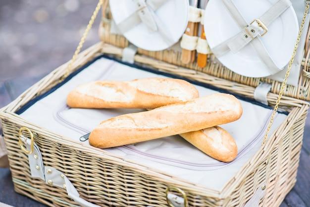 公園の木製テーブルの上にパンを入れたピクニックバスケットを開きます。 Premium写真