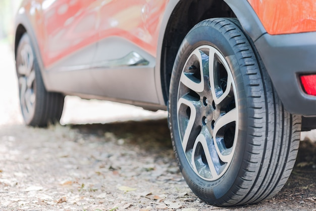 車のタイヤのクローズアップ。秋の紅葉で覆われた道路上の駐車中の車の背面図。 Premium写真