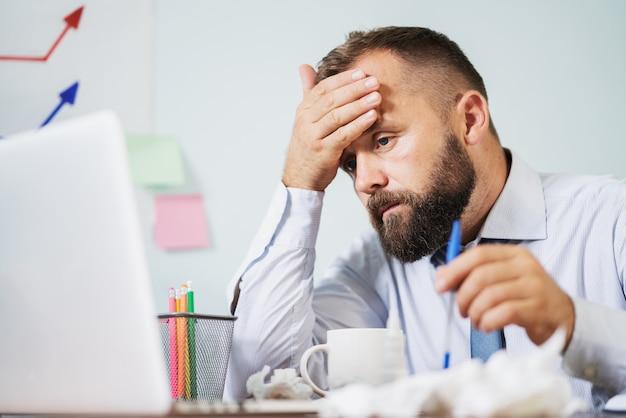 Человек с гриппом работает в офисе Premium Фотографии