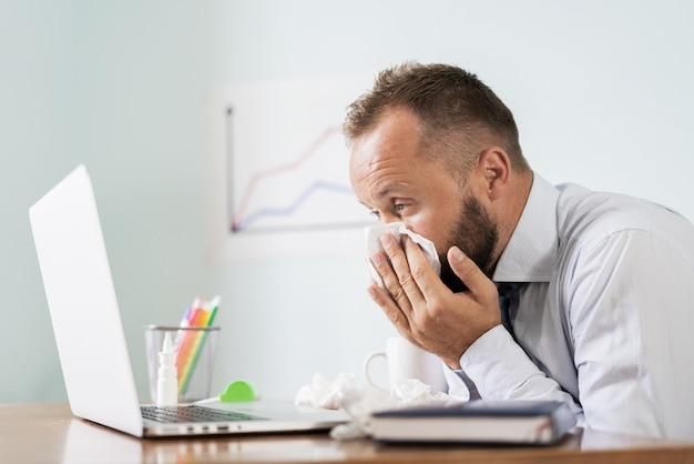オフィスで働いている間に鼻をかむくしゃみを持つ病気の人、ビジネスマンは風邪、季節性インフルエンザをキャッチしました。 Premium写真