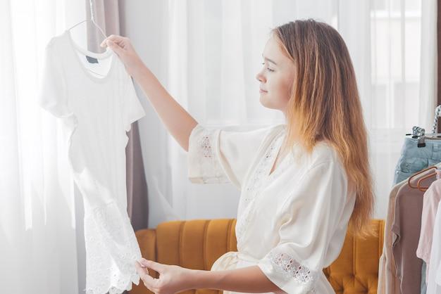 女性の家のワードローブで服を選ぶ Premium写真
