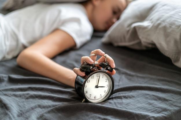 眠ろうとしている枕の下に頭を抱えてベッドに横たわっている不眠症の女性。 Premium写真