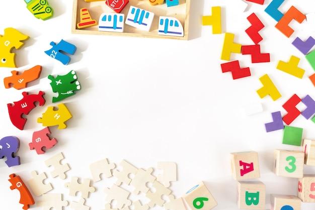 白地にカラフルな赤ちゃん子供のおもちゃ。カラフルなブロック、車、飛行機、パズルの開発からフレーム。上面図。フラット横たわっていた。テキストのスペースをコピー Premium写真