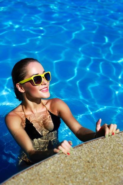 プールでポーズハッピー日焼けした女の子 無料写真