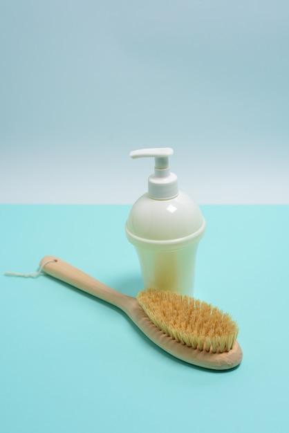 乾いたボディマッサージのためのアンチセルライトブラシ、白いボトルのアロマセラピー石鹸 Premium写真