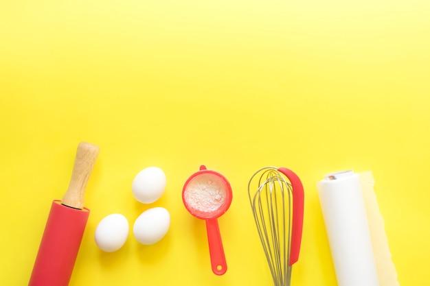 明るい黄色の背景にベーキングと食材のキッチンデバイス。トップビュー、コピースペース。テキストのための場所。 Premium写真