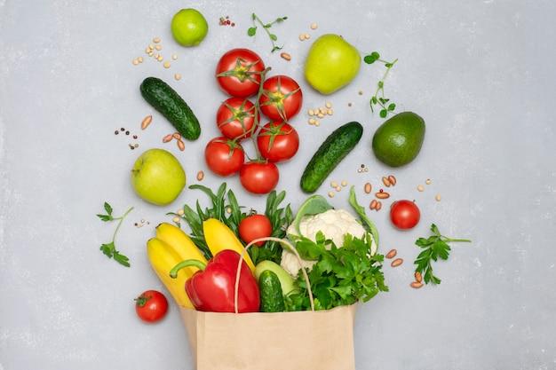 Бумажный мешок, полный овощей и фруктов крупным планом вид сверху. здоровая пища, концепция покупок, сыроедение. Premium Фотографии