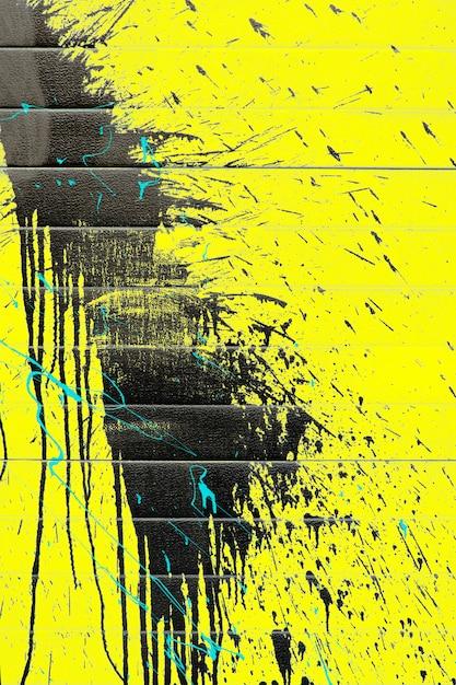 Брызги черной краской на желтом фоне стены Premium Фотографии